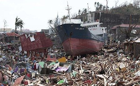 Super typhoon Haiyan: survivors walk past a ship that lies on top of damaged homes
