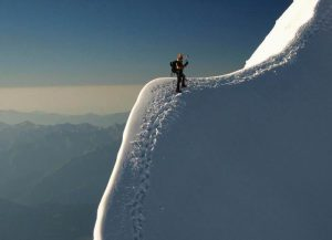 man-climbing-snowy-mountain