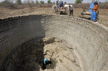 Villagers collect water from a nearly dry well at Jainoor village